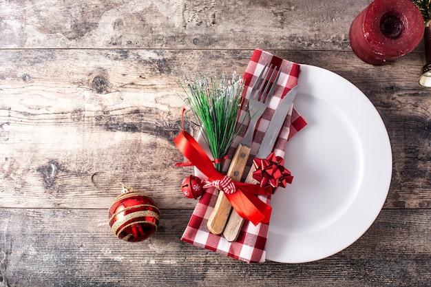 Вилка, нож и рождественские украшения на деревянных фоне
