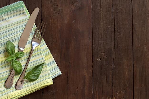Вилка, нож, базилик и салфетка на деревянном столе