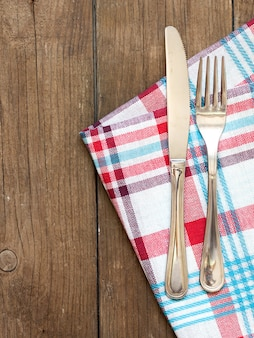 Fork and knife on kitchen towel and old wooden table top view with copy space