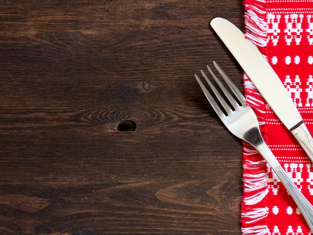 Fork and knife on kitchen towel on a wooden table top view