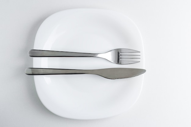 The fork and knife lie on a white plate