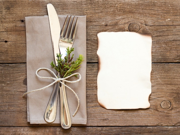 Fork and knife on a napkin on an old wooden table top view with copy space