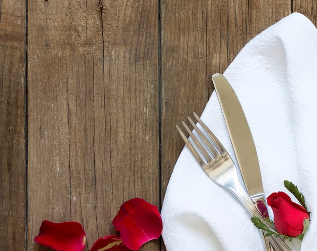 Fork and knife on napkin and old wooden table top view with copy space