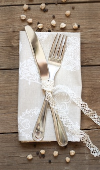 Fork and knife on a napkin on an old wooden table top view