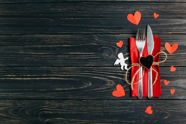 Fork and knife on napkin with paper hearts