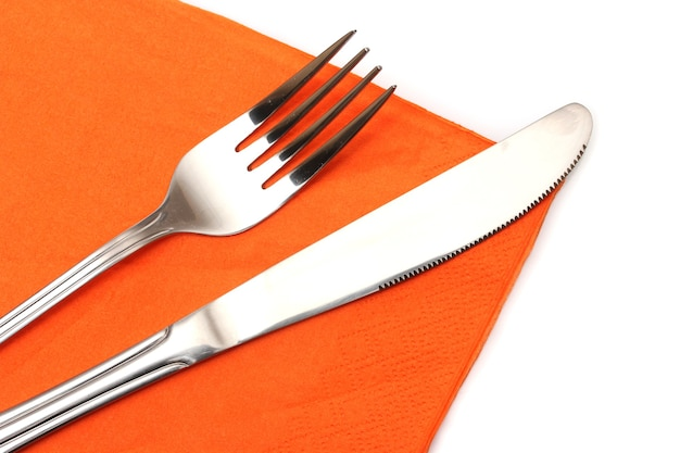Fork and knife in a orange cloth on white
