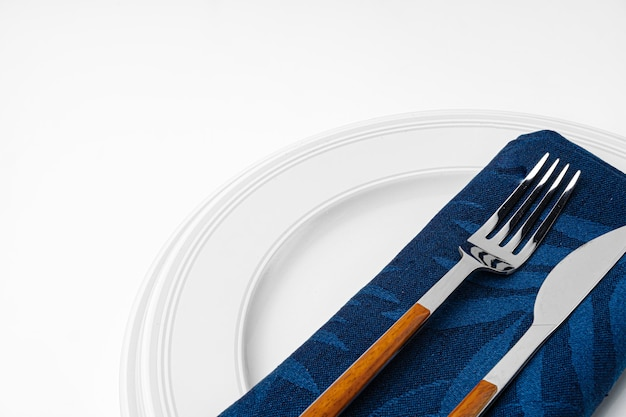 Fork, knife and plate on towel. isolated on white background. close up.