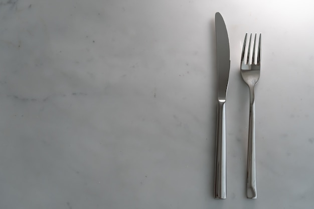 Fork and knife on white marble texture background. concept for food and dining tableware
