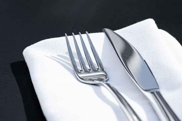 Fork and knife with white napkin on table in luxury restaurant outdoors fine dining menu for wedding...