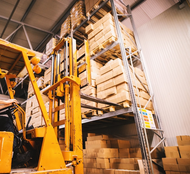 Fork lifter approaching pallet filled with stacks of boxes on a rack in storage area.