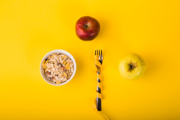 Fork in measuring tape between apples and bowl of flakes