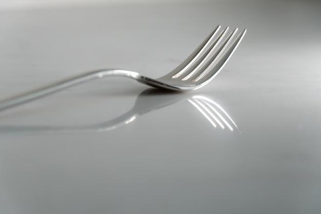 Вилка на фоне белой мраморной текстуры. концепция еды и столовой посуды
