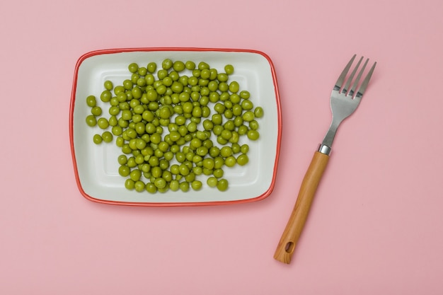 Fork and plate with canned green peas on a pink background. dietary vegetarian food.