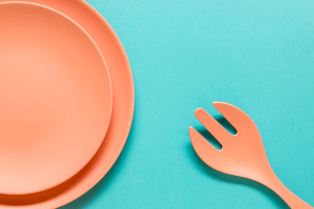 Fork and plates on blue background