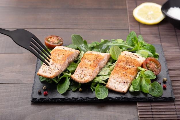 Вилка прокалывает филе лосося на грифельной тарелке на фоне деревянного стола.