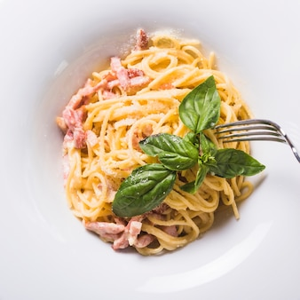 Fork over the spaghetti with meat and basil leaf on plate