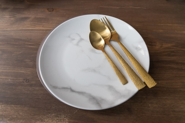 Fork, spoon and plate on wooden table in restaurant.marble plate, gold knife,fork and spoon on wooden background.dishes and cutlery, plate with spoons and fork. cooking concept.copy space