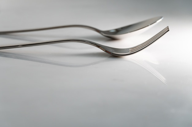 Fork and spoon on white marble texture background. concept for food and dining tableware