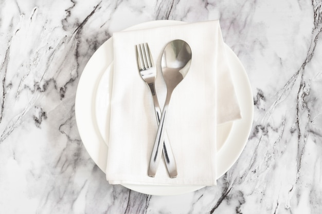 Fork and spoon with a napkin on plate on marble surface