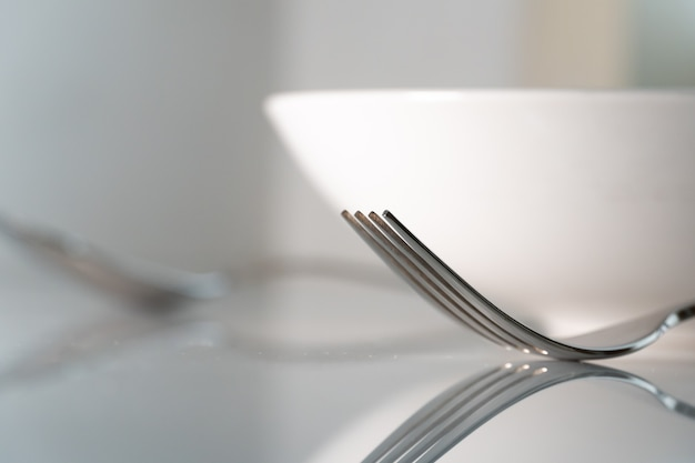 Fork and spoon with white dish on white marble texture background. concept for food and dining tableware