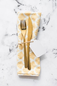 Fork; table knife and napkin tied with blank white tag and string on marble textured background