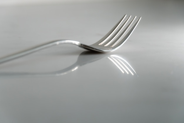 Fork on white marble texture background. concept for food and dining tableware