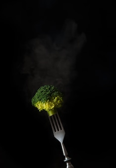 Fork with boiled broccoli and steam on a black background, copy of space