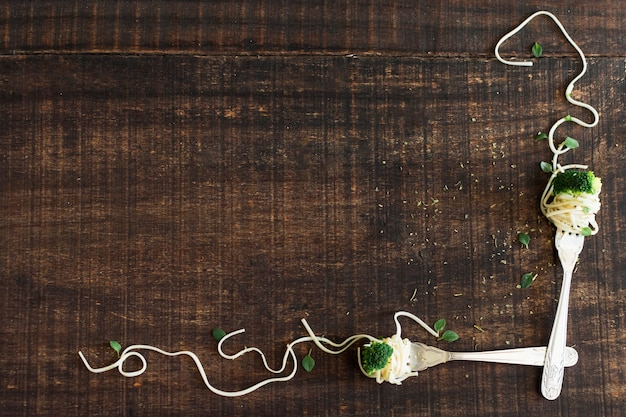Fork with broccoli and noodles on wooden textured background