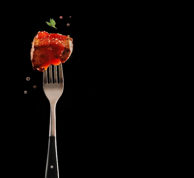 Fork with delicious steak piece with ketchup and spices on black background