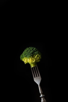 Fork with fresh broccoli on a black background, copy space