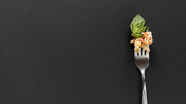 Fork with fusilli pasta and basil leaves over black background