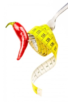 측정 테이프 및 칠리 페 퍼와 포크. 자연적인 체중 감소의 개념입니다. 선택적 초점을 닫습니다.