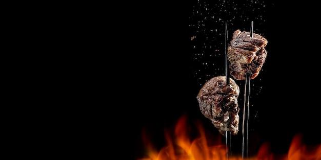 Вилка с кусочками вкусного мяса, приготовленного на гриле на черном фоне. вкусные кусочки свинины на крупном плане вращающейся вилки. жареные кубики свинины на вилке. вкусное мясо. место для текста. длинный широкий баннер