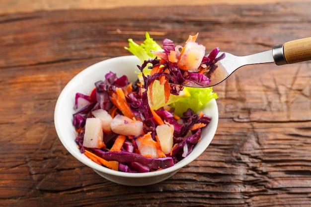 Вилка с салатом в женской руке над тарелкой медленного салата из капусты на деревянном фоне. горизонтальное фото