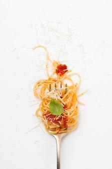 Вилка со спагетти, томатным соусом и листом базилика на светлой поверхности. выборочный фокус. вид сверху.