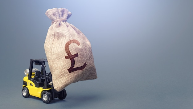 Forklift carrying a british pound sterling money bag. strongest financial assistance