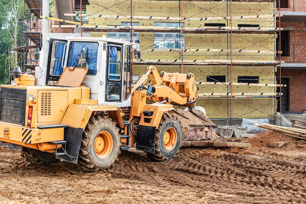 A forklift at a construction site is lifting a reinforced concrete slab. construction machine. construction of a brick building and thermal insulation with mineral wool.