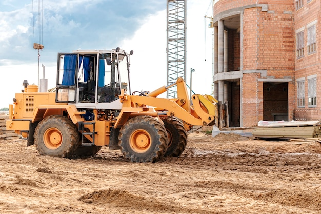 A forklift at a construction site is lifting a reinforced concrete slab.