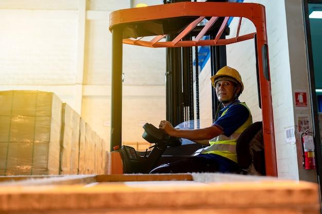 창고에 노란색 안전모를 쓴 안전 점프수트 유니폼을 입은 지게차 운전사 아시아 노인. 카메라를 보고 지게차 로더 작업에서 웃는 작업자 남성 수석