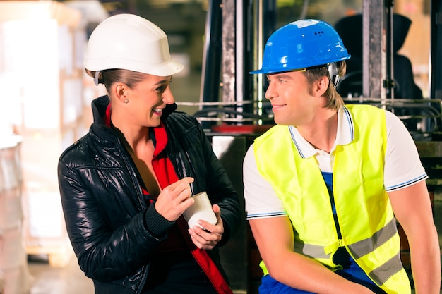 Forklift driver and female coworker takes a break at warehouse of freight forwarding company