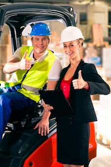 Forklift driver and female super visor with clipboard at warehouse of freight forwarding company, thumbs up