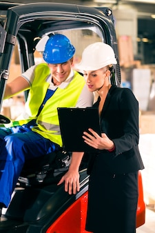 Forklift driver and female super visor with clipboard at warehouse of freight forwarding company