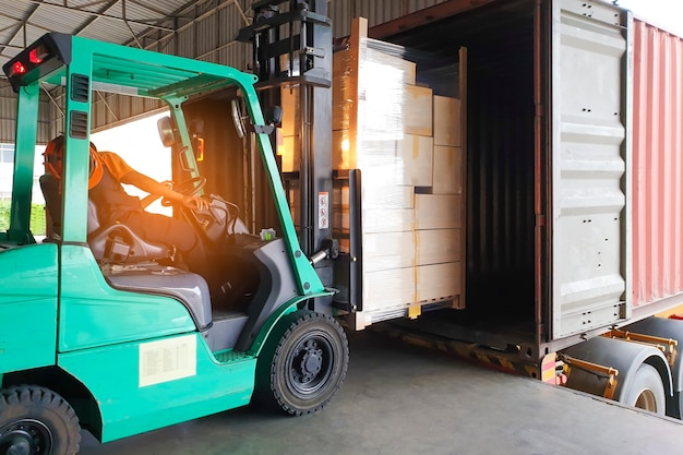 Forklift driver loading cargo pallet shipment into a truck container