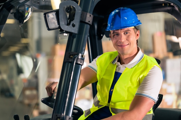 Forklift driver in protective vest and forklift at warehouse of freight forwarding company,