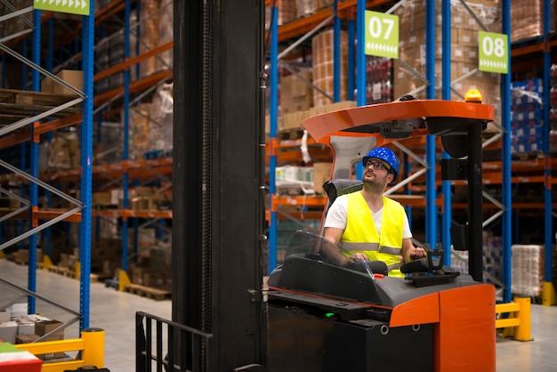 Водитель погрузчика перемещает и поднимает товары в большом складском центре