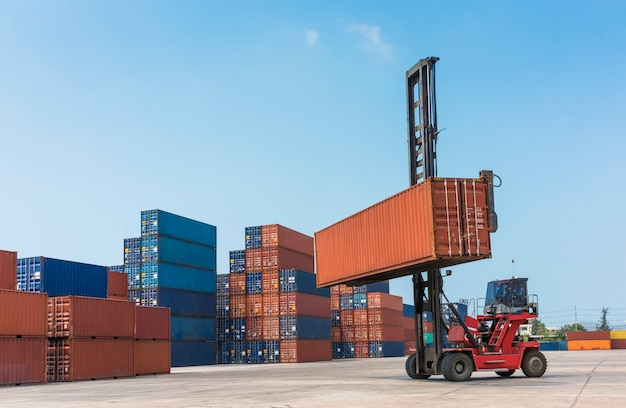 Forklift handling container box in import, export, logistics area with empty sky for add some text, logo, image, etc.