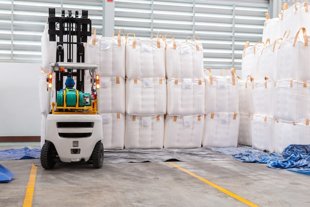 Forklift is handling jumbo bags in large warehouse.