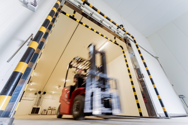 Forklift in a large industrial freezer warehouse. empty warehouse for vegetable storage.