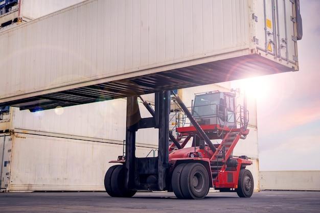 물류 수입 수출 및 운송 비즈니스 산업을 위한 지게차 적재 흰색 컨테이너 상자입니다. 도크에 있는 화물 트럭 컨테이너 운송은 산업용 크레인이 있는 화물선입니다. 프리미엄 사진