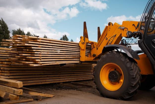 Вилочный погрузчик загружает доски на складе пиломатериалов на открытом воздухе. автозагрузчик работает на складах лесопильных заводов, деревообрабатывающей промышленности, столярных изделиях. обработка древесины на заводе, лесопилка, лесопилка
